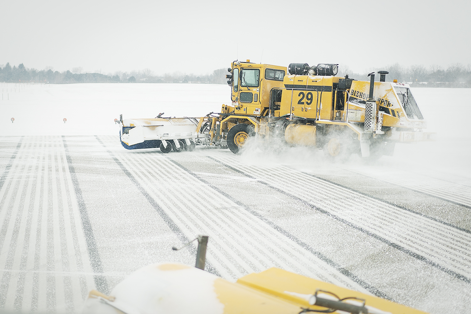 A broom truck, using massive brushes and a blower clears snow from the runway at Bishop International Airport.