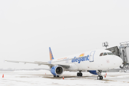 An airplane, part of the Allegiant fleet, waits on the tarmac to be boarded and loaded with luggage at Bishop International Airport.