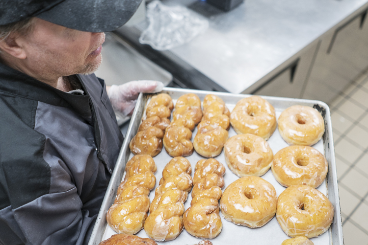 Bruce Sowles, 53, of Flint, carries a tray of fresh donuts to prepare them for delivery at Blueline Donuts, inside of Carriage Town Ministries.