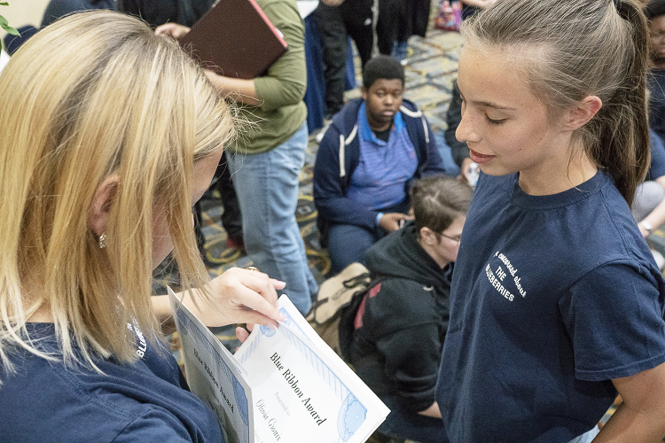 Flint, MI - Friday, May 4, 2018: University of Michigan - Flint student Carryn White, 19, from Burton hands out a Blue Ribbon Award to Olivia Grouix, a student at Flushing Middle School, during the 5th Annual Blueberry Ambassador Awards Party at the