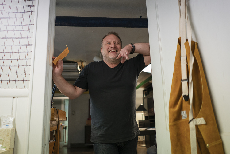 Flint, MI - Tuesday, May 8, 2018: Flint resident and metalsmith Robert McAdow laughs as he leans on the doorway to his soldering area in his studio.