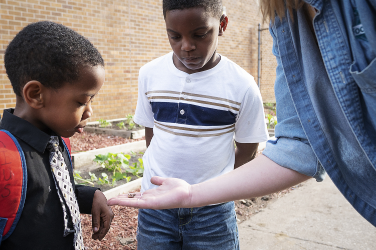 Khaterius Cannon, 5, and Jaelyn Millender, 7, inspect a worm held by a FoodCorps service member.