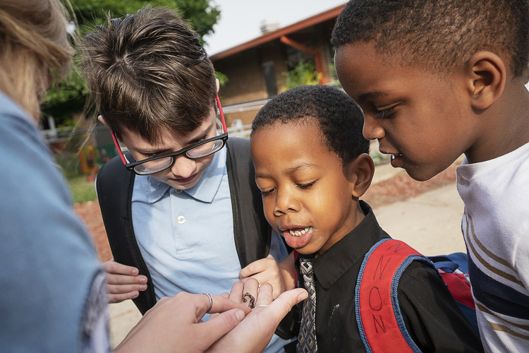 Students (from left) Alex Grant, 10; Khaterius Cannon, 5; and Jaelyn Millender, 7, inspect a worm.