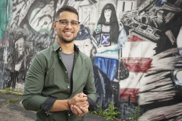 Flint, MI - Tuesday, June 19, 2018: Burton resident and director of the Hispanic Technology and Community Center of Flint, Asa Zuccaro (26) has his photograph taken in front of a large mural on the outside of the building at the Hispanic Technology a