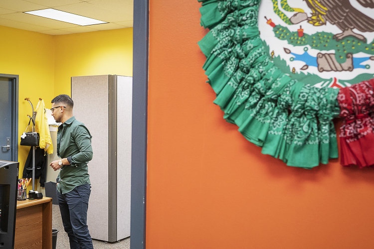Flint, MI - Tuesday, June 19, 2018: Asa Zuccaro (26) from Burton, the director of the Hispanic Technology and Community Center of Flint, speaks with a staff member at the Hispanic Technology and Community Center of Flint.