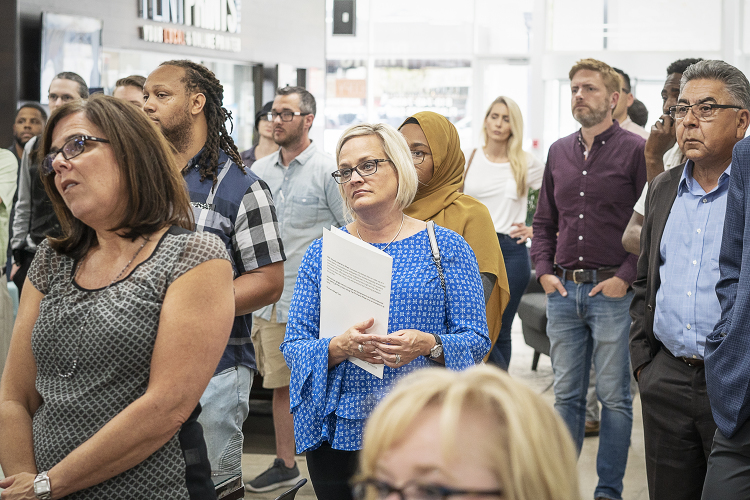 Flint, MI - Thursday, June 22, 2018: Choice Office Products sales representative Julie Cauley (47) from Flint, center, listens to the speakers during the move-in party presentation at The Ferris Wheel in Downtown Flint.