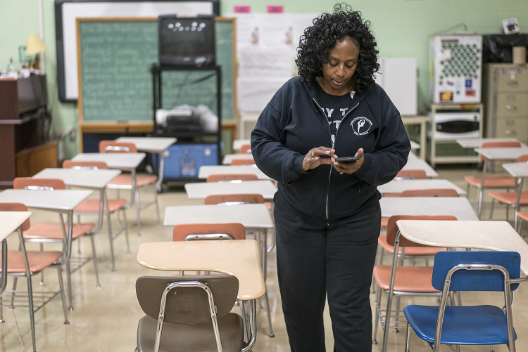 Walking between rows of empty desks in her classroom at Flint Northwestern High School, Sheila Miller-Graham checks her phone for messages before putting away homecoming decorations. Between teaching at Flint Northwestern and running Creative Express