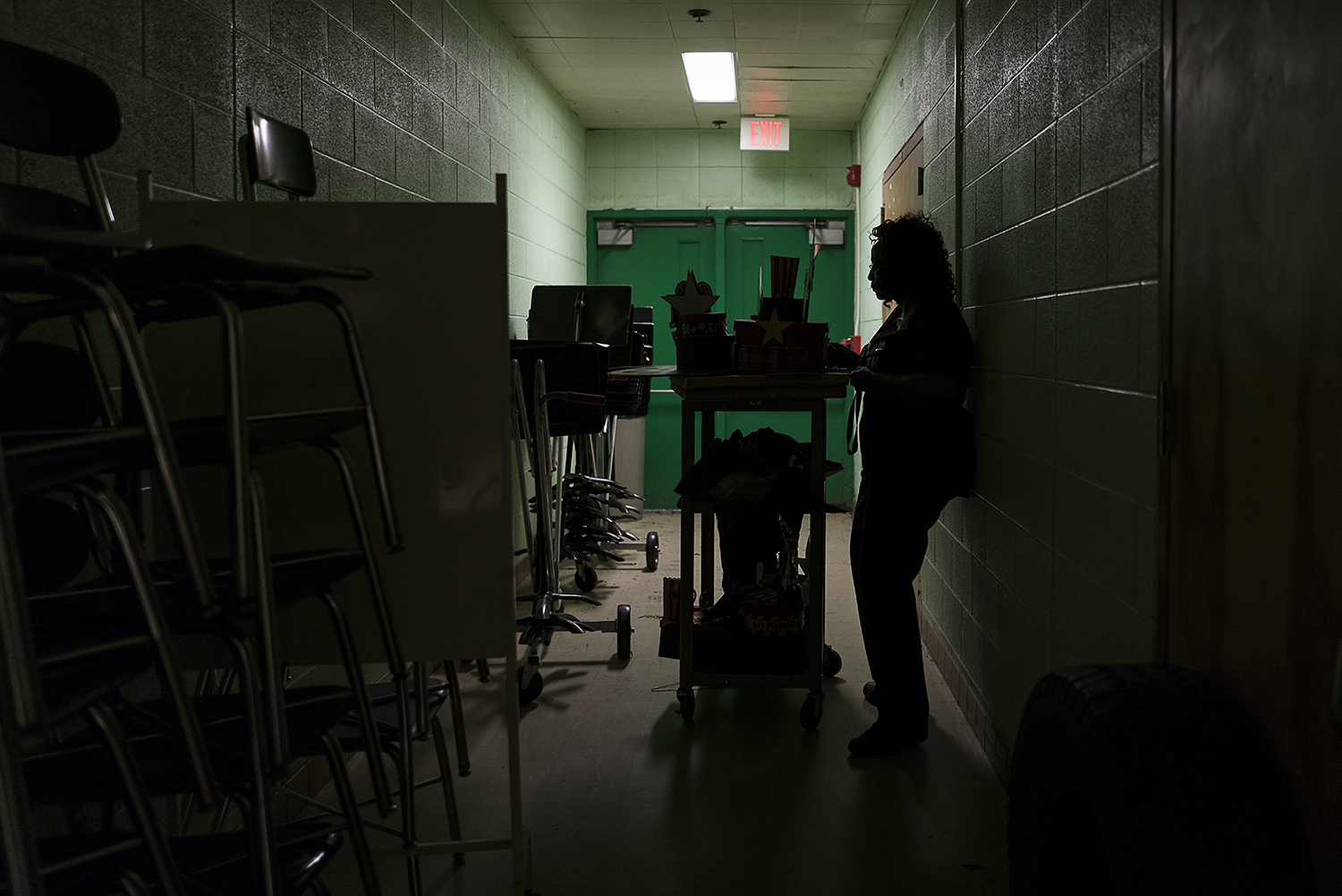 In a dimly lit corridor between the band room and auditorium at Flint Northwestern High School, Sheila Miller-Graham stands by her cart loaded with decorations for homecoming.
