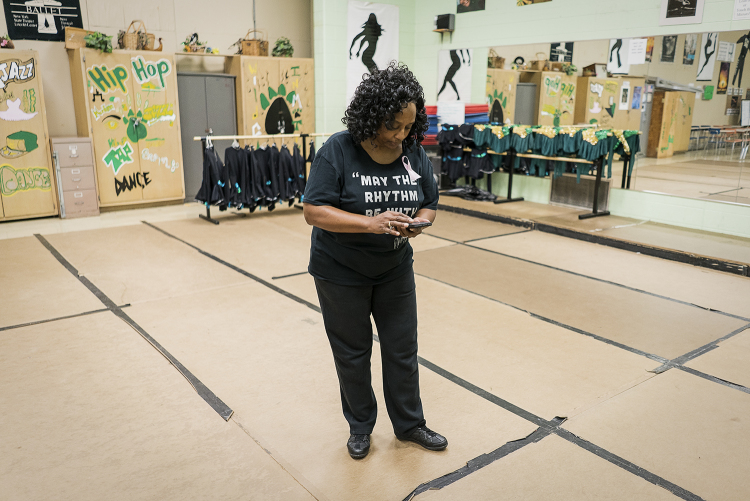 With work still to be done, Sheila Miller-Graham checks her phone while on the dance floor of her classroom at Flint Northwestern High School. Miller-Graham wears many hats between the high school, her dance studio and her church. She considers givin