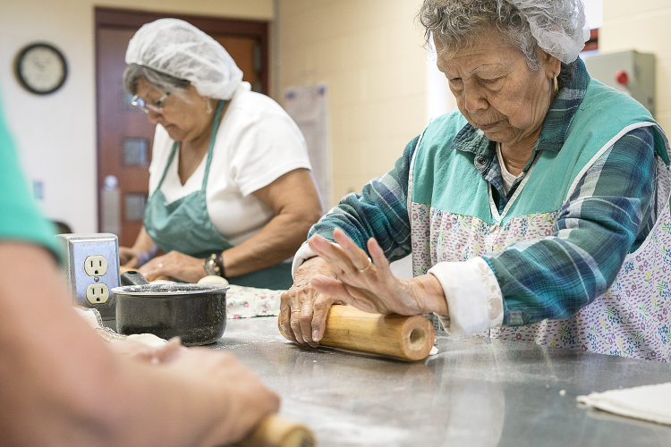 Jane Rubio, 73, of Burton (left) and Lupita Vargas, 87, of Flint, roll out balls of masa before placing them on a tray to head to the cooktop in the San Juan Diego Activity Center kitchen at Our Lady of Guadalupe.