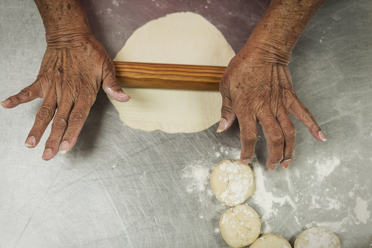 Ofelia Luna, 79, of Flint, rolls out masa to make tortillas, a weekly tradition at Our Lady of Guadalupe Catholic Church.