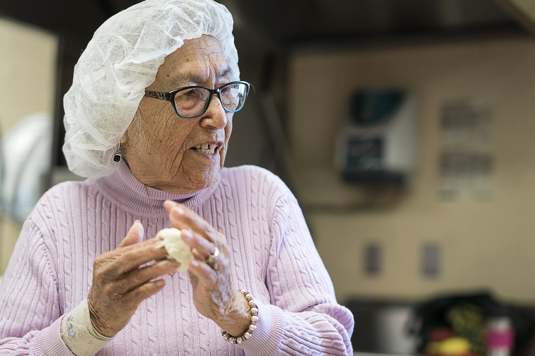 Linda Quintanilla, 90, of Flushing, rolls a small ball of masa between her hands as she chats with the other women making tortillas in the kitchen at the San Juan Diego Activity Center.