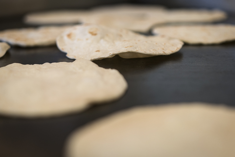 Homemade flour tortillas bubble and brown on the cooktop in the kitchen at the San Juan Diego Activity Center at Our Lady of Guadalupe Catholic Church.