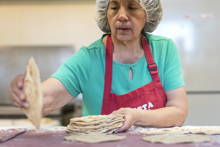 Flint resident Connie Rosas, 72, collects and stacks tortillas to be packaged after they have cooled.