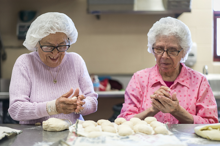 Linda Quintanilla, 90, of Flushing, (left) laughs as she rolls balls of masa and chats with Connie Aguilar, 81, of Flint, at Our Lady of Guadalupe's Tortilla Factory.
