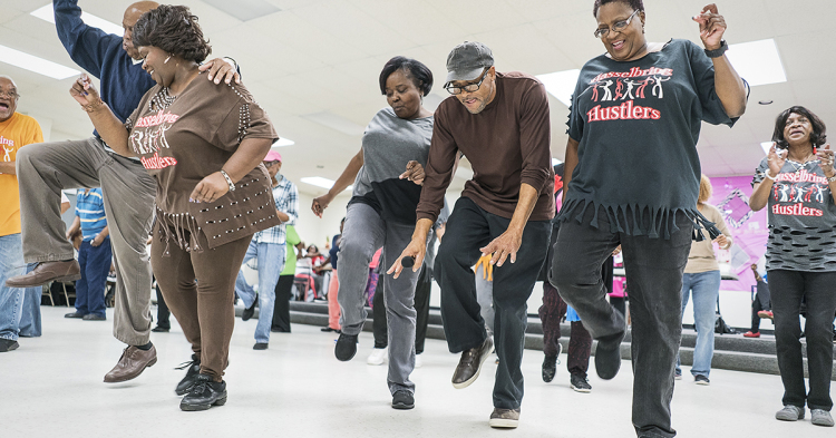 "Gardell Haralson, 64, of Flint (center right) takes a break from emceeing to dance with the Hustlers at the Hasselbring Senior Community Center. ""It gave me the feeling I was doing something,"" he said about the progress of the Hustlers. ""They're not"