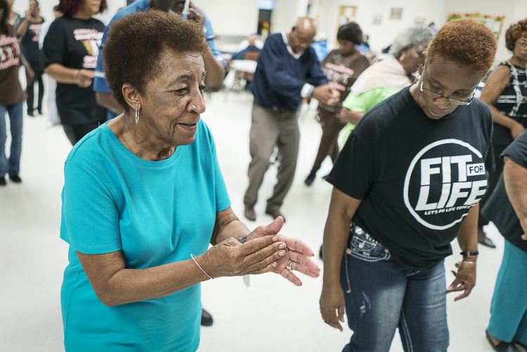 "Flint residents Ruth Morris, 82, (left) and Queenella McGee, 66, dance together at the Hasselbring Senior Community Center. ""I love coming because of these people,"" Morris says. ""They're my sisters and brothers."""