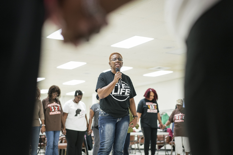 Queenella McGee, 66, of Flint leads the Hasselbring Hustlers in prayer before they finish their dancing for the day at the Hasselbring Senior Community Center.