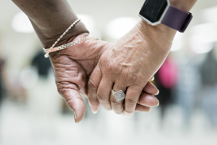 Two Hasselbring Hustlers hold hands during the closing prayer after nearly two hours of dancing at the Hasselbring Senior Community Center.