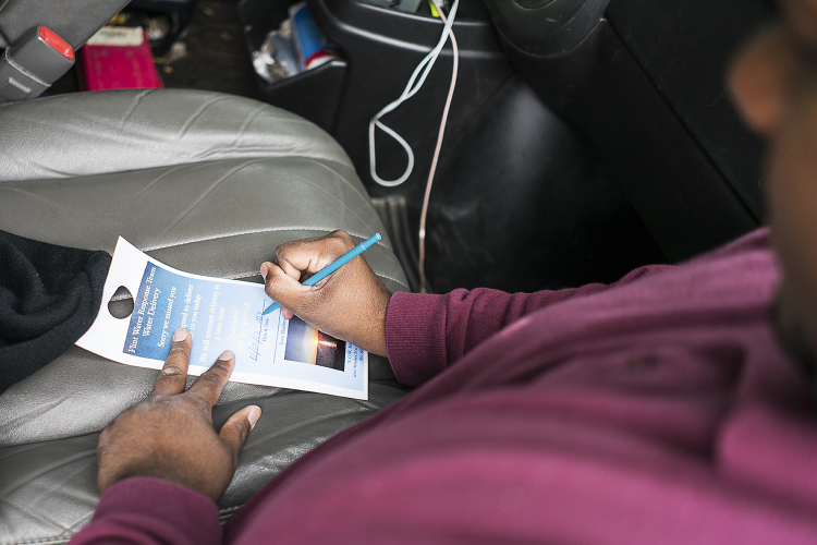 Flint resident William Harris, 31, leaves a note to let residents know that a water delivery was attempted at their home. His team visits between 60 and 70 homes each day. Water delivery is available for residents who cannot making it to the water di