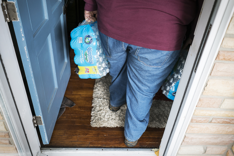 William Harris, 31, of Flint, carries two cases of water into a home of a resident in the 4th Ward.