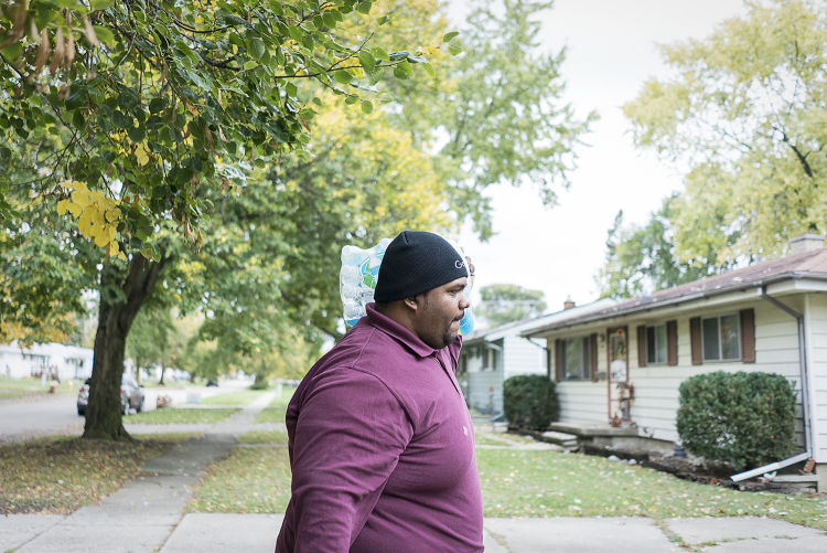 With a case of water bouncing on his shoulder, Flint resident William Harris, 31, walks up the sidewalk to a home on the eastside of Flint.