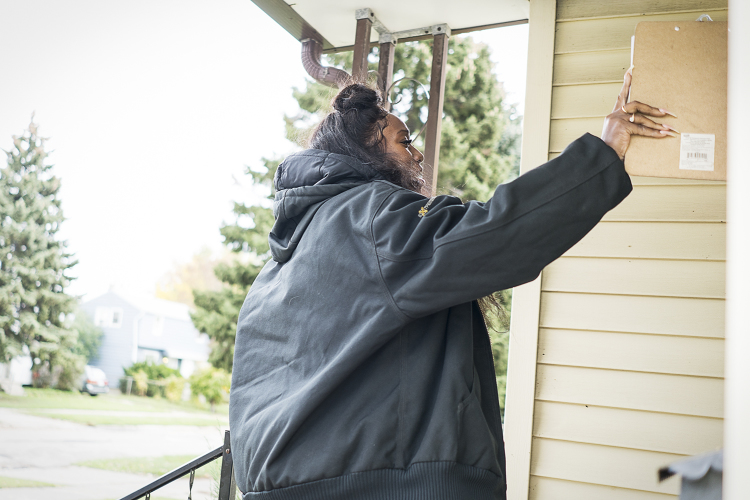 Gently rapping on the storm door, Flint resident Shadae Johnson, 26, approaches 60 to 70 homes each day on her team's water delivery route. She requests signatures to document the amount of water delivered to each home.
