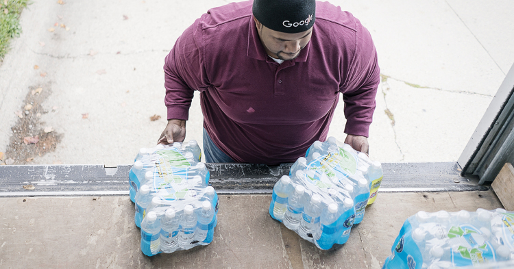 William Harris, 31, of Flint, slides two cases of water off the back of his team's delivery truck on Flint's eastside. The team from Asbury United Methodist deliver water to 60 to 70 homes on their route.