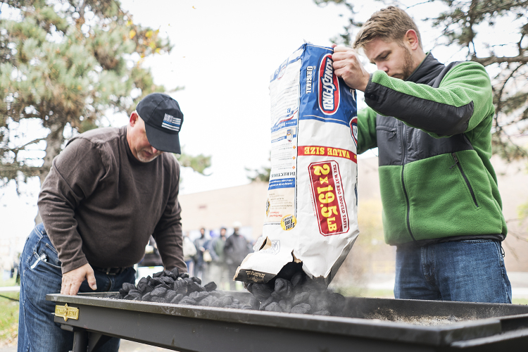 Volunteers Steven Moore, 52 (left) of Davison, and Steven Elkins, 27, of Flint, prepare the grill at Riverbank Park for the Flint Community Cookout. They generally grill 300 burgers and more than 100 hot dogs at each cookout.