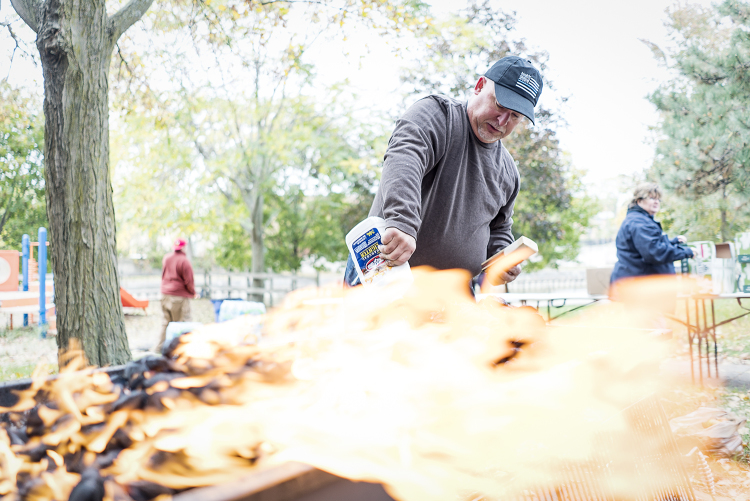 Volunteer and Davison resident Steven Moore, 52, squeezes lighter fluid onto a pile of charcoal briquettes as he prepares the grill for the Flint Community Cookout.