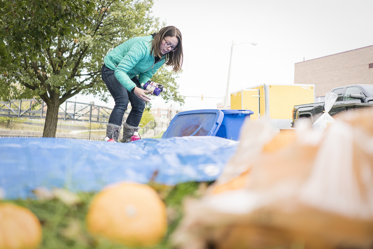 Co-organizer and Flint resident Sarah Elkins, 28, sets up a station for pumpkin painting at the Flint Community Cookout in the Riverbank Park.