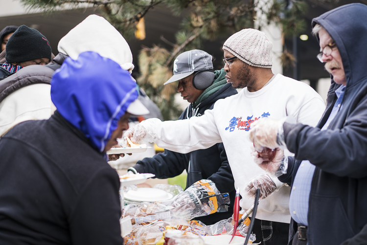 "Burton resident Paul C. Owens, 31, (center) serves up some food at the Flint Community Cookout at the Riverbank Park. Owens, a volunteer for 4 years, uses the cookouts as an opportunity to ""do the Lord's work"" and to meet people, overcoming his self-"