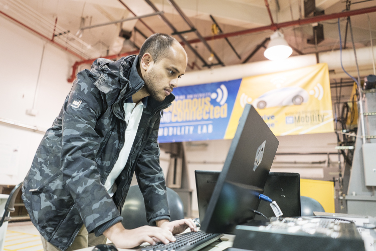 Flint, MI - Friday, November 10, 2017: Shobit Sharma, 26, one of two student coordinators for the SAE/GM AutoDrive Competition checks a connection between the server and Chevrolet Bolt electronic car in the garage at Kettering University.