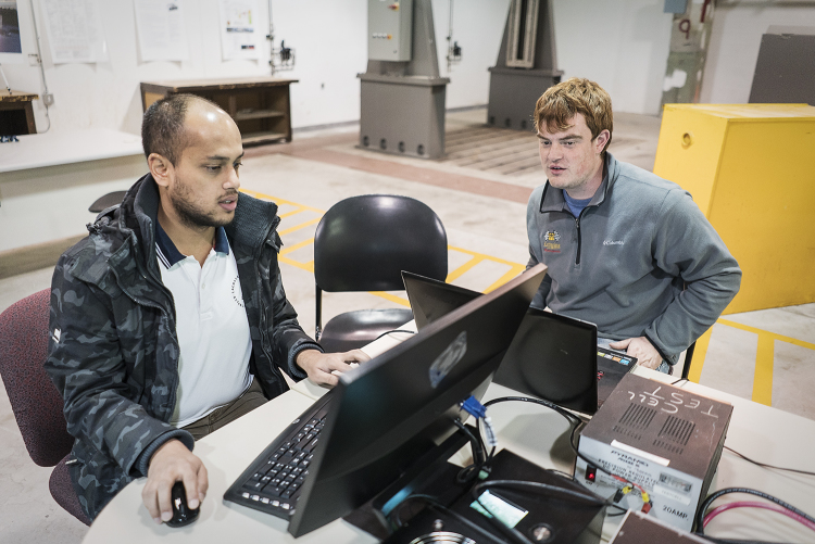 Flint, MI - Friday, November 10, 2017: Project coordinators Shobit Sharma, 26 (left), and Alex Rath, 22, verify the connection between the server and Chevrolet Bolt in the garage at Kettering University that is being used to house the vehicle for the