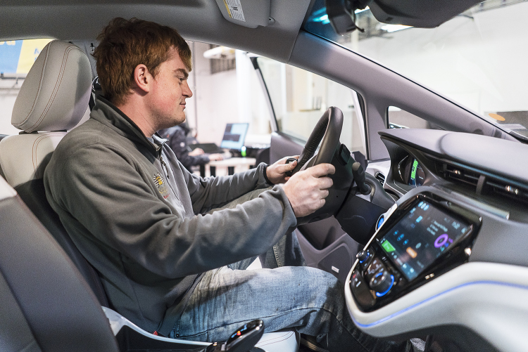 Flint, MI - Friday, November 10, 2017: Graduate student and student coordinator for the SAE/GM AutoDrive Competition, Alex Rath, 22, sits in the driver's seat of the new Chevrolet Bolt and surveys the driver information center as it is connected to a