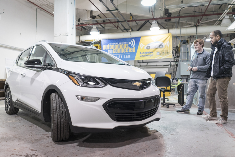 Flint, MI - Friday, November 10, 2017: Student coordinators for the SAE/GM AutoDrive Competition Alex Rath, 22 (left) and Shobit Sharma, 26, survey the new Chevrolet Bolt provided to the university for the competition in the garage at Kettering Unive