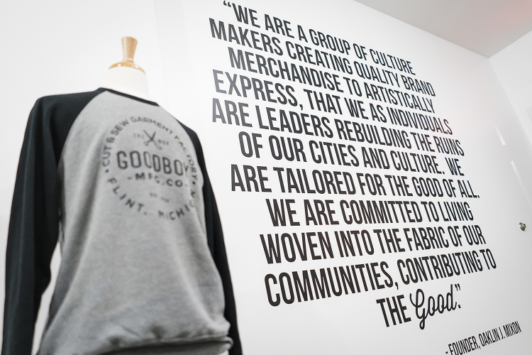Vinyl graphics, photographs and other decorations are hung on the walls of the new GoodBoy Clothing showroom in preparation for the upcoming grand opening event on Friday, November 17, 2017 at GoodBoy Clothing in downtown Flint.