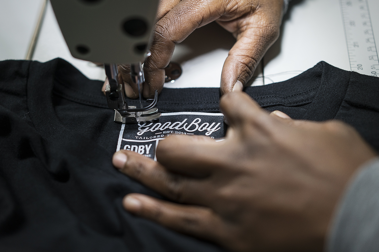 GoodBoy Clothing textile expert Tameka Davis, 37, of Flint, stitches tags into new shirts that are headed to the showroom at the new GoodBoy Clothing storefront in downtown Flint.