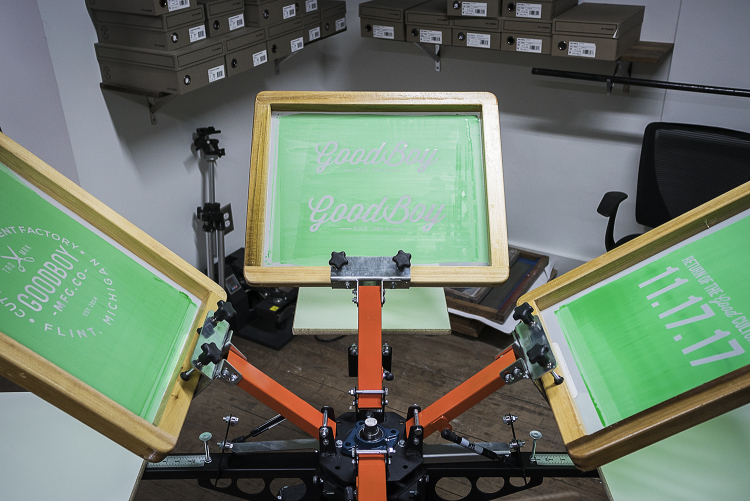 A four station screen printing press waits at the ready in the production area of the new GoodBoy Clothing storefront in downtown Flint.