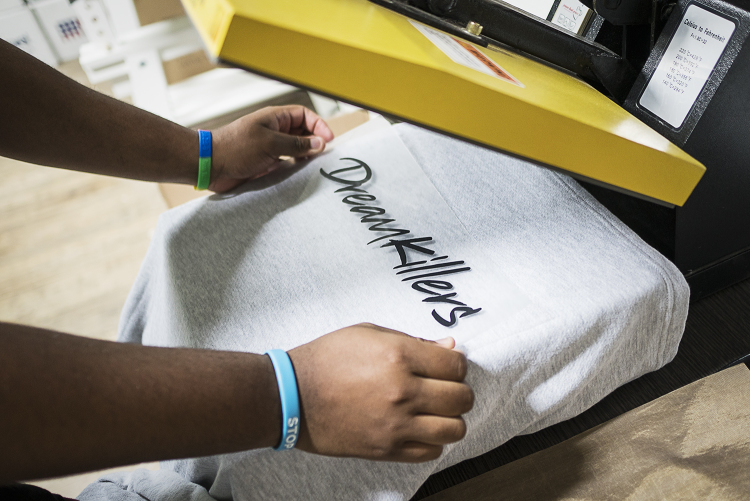 In the production area of the new GoodBoy Clothing storefront in downtown Flint, production manager Andre McGee, 23, of Flint runs application tests of vinyl lettering onto clothing garments in preparation for the grand opening event on Friday, Novem