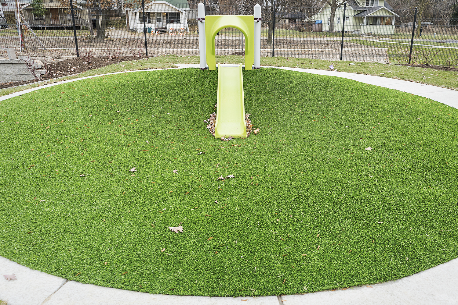 Flint, MI - Tuesday, November 21, 2017: A small slide drops down into a lush field of green grass outside of the new Educare Center in Flint.