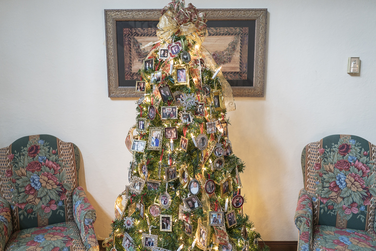 A Christmas tree adorned with portraits and ribbon stands in the foyer of the Heddy residence.