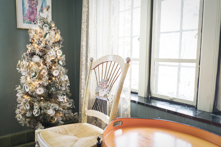 A small Christmas tree decorated with miniature tea cups and saucers sits in the corner of a room in the Heddy home.