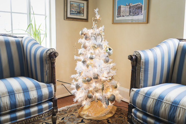 "Sitting in the corner of the ""Flint Room"" of the Heddy house, is a small, white and gold Christmas tree that was presented to the Heddy's for their 50th wedding anniversary."