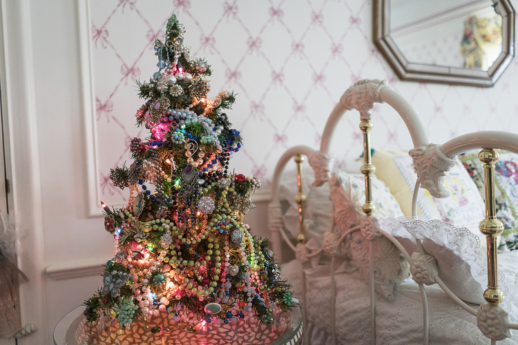 A miniature Christmas tree adorned with the jewelry of a passed relative stands on a table in one of the many rooms in the Heddy home.