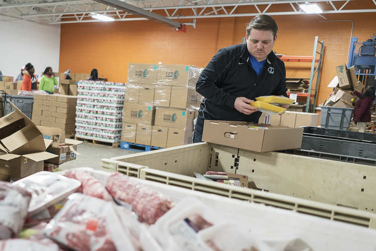 "Andrew Smith, 31 of Lansing, sorts frozen meat into large bins that will be delivered to affiliated agencies at the Food Bank of Eastern Michigan. Smith, volunteering with a group of co-workers, says he and his co-workers like ""to help in the communi"