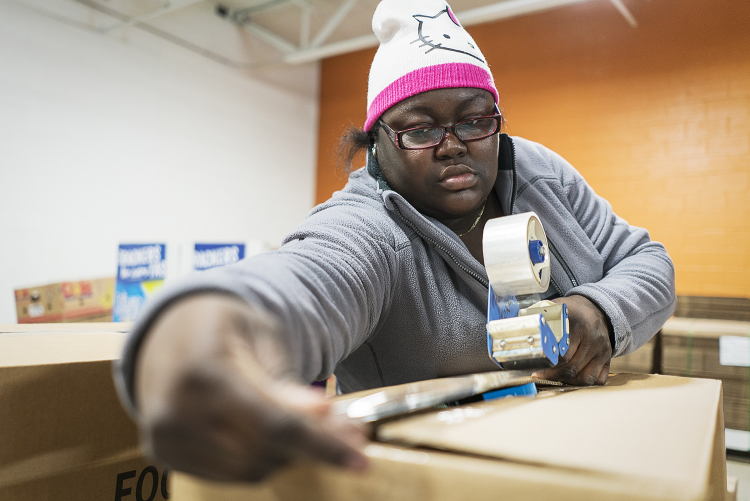Jacquece Dent, 38, of Flint, tapes a large box full of food for a family holiday meal before it is loaded up and shipped out from the Food Bank of Eastern Michigan.