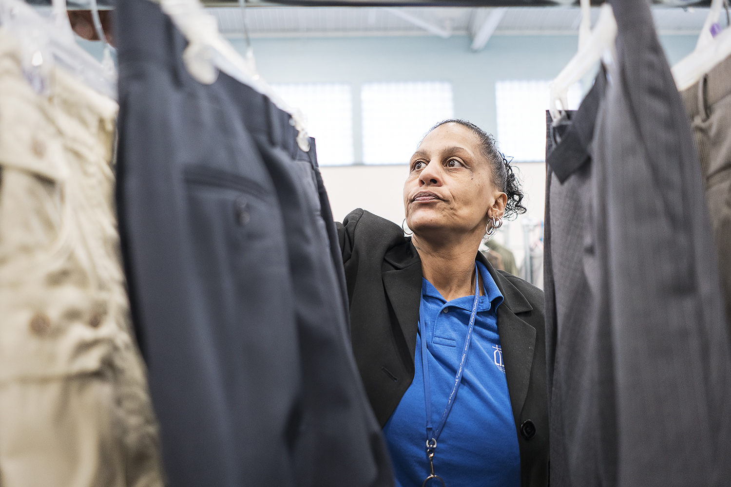 Community Closet Coordinator at the Catholic Charities Center for Hope Redonna Riggs, 47, of Flint, organizes donated clothing hanging from a clothing rack.