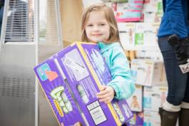 The Food Bank of Eastern Michigan helps distribute the 1.2 million diapers to needy families. Shown here: A girl makes a donation during the annual Diaper Drive in May 2017.