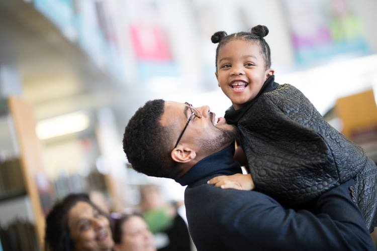 Isaiah Oliver picks up daughter Carrington, 4, after his MLK Day speech at Flint Public Library.
